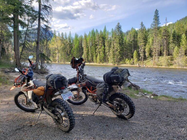 motorcycles loaded for camping by river